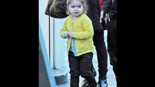 Harper Beckham wears a yellow cardigan to brighten up a day out with Victoria and Romeo