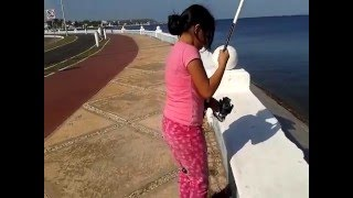 Little girl catches your first fish (needle fish)