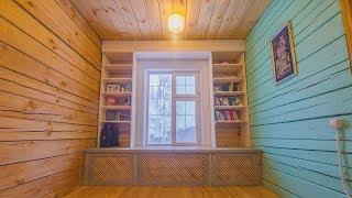 Окно с большим подоконником и полками для книг.