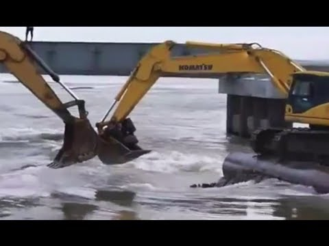 Crazy ferry video: Russians cross river in backhoes
