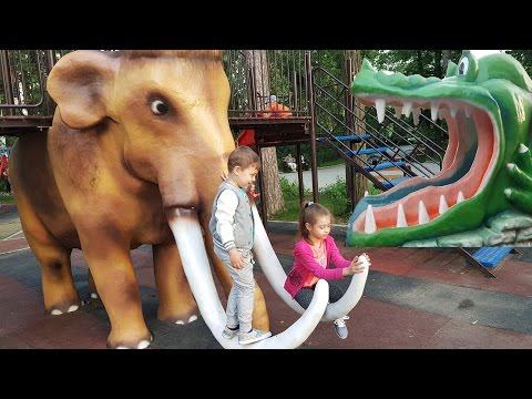 Outdoor playground fun for kids in the park.  Sliders with dinosaurs, mammoths, elephants...
