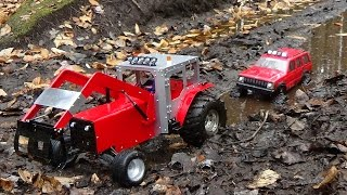 Rc tractor pulling a jeep cherokee caught in the mud.