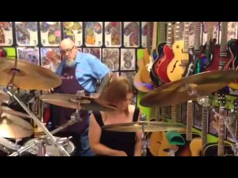 Chick with Sticks Playing Drums at Tattoo Teds shop