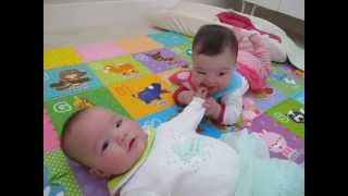 7 month old fraternal twin girl eating her sister's hand