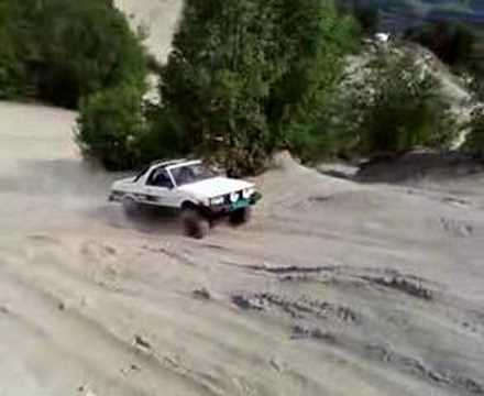 "6"" lifted subaru brat with 29"" superswampers driving in the sands."