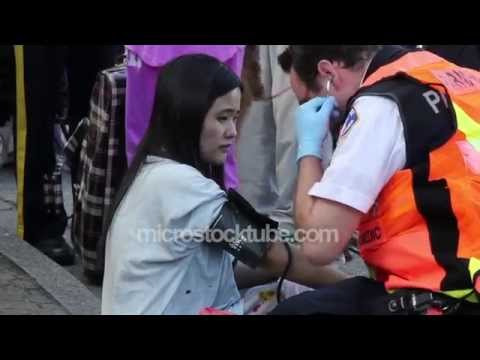 Paramedic helping Asian female burn victim