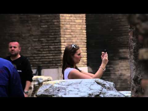 Tourists walking around taking pictures in the Colosseum in Rome, Italy.