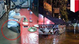 Foto viral pria makan di tengah-tengah banjir - TomoNews