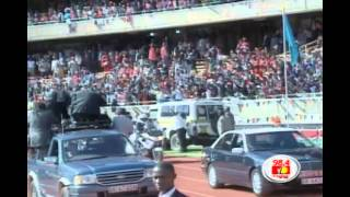 Uhuru waves the crowd aboard a ceremonial Land Rover
