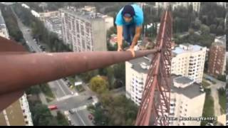Russian daredevil takes his life in his hands as he hangs like a monkey off 1,000ft crane