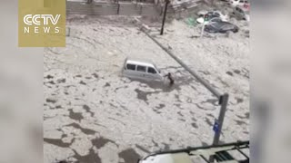 Footage: Heavy rain and hail turn streets into rivers in NE China