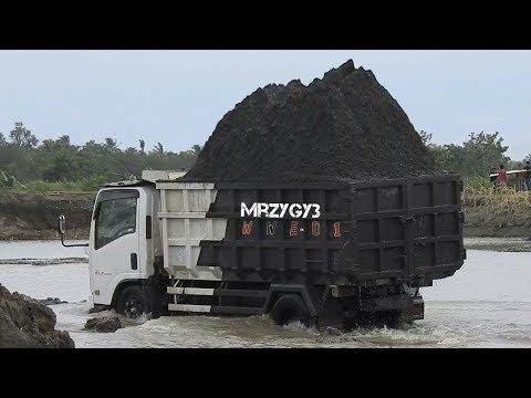 Overloaded Dump Truck On The River By Kobelco SK200-10 Keihatsu 921C Excavator