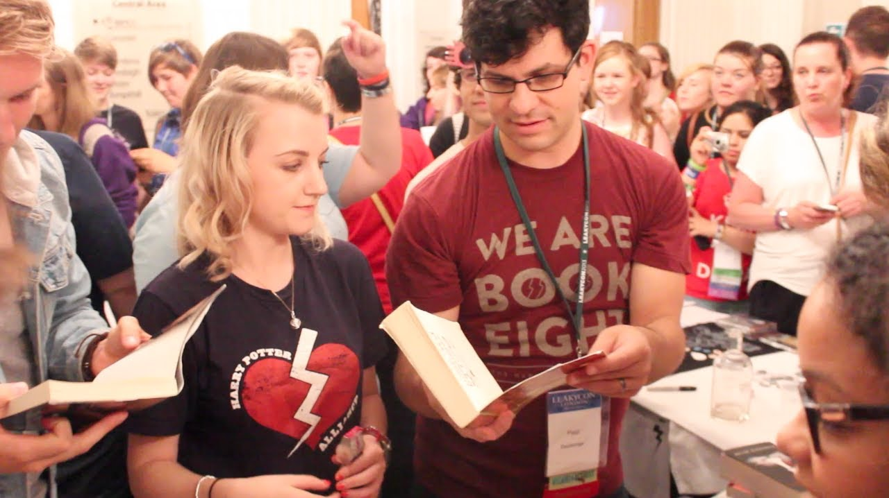 Evanna Lynch and members and volunteers of the HPA are doing a book swap in a crowded place. She is wearing a HPA T-shirt and there are books in people's hands.