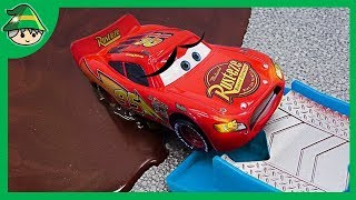 Disney Lightning McQueen car crosses the railroad track. The car is in a muddy puddle.