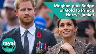 Meghan pins Badge of Gold to Prince Harry's jacket
