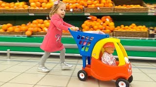 Funny Kid and Baby Born Doll doing shopping at the Supermarket