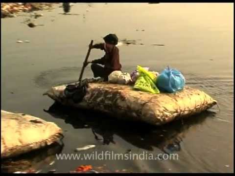 Rag picker rows on a raft made of sacking and polystyrene, Yamuna!