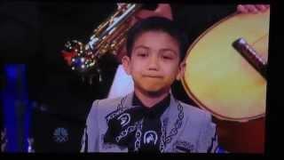 Niño cantando en concurso con mariachi