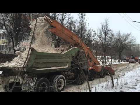 Снегоуборочный комбайн загружает снег в самосвал КамАЗ в Калуге