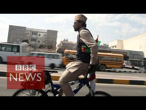 Riding a bike backwards around the world for peace - BBC News