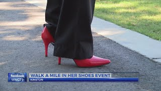 "Men walk in red heels for domestic violence awareness ""Walk a Mile in her Shoes"" event"