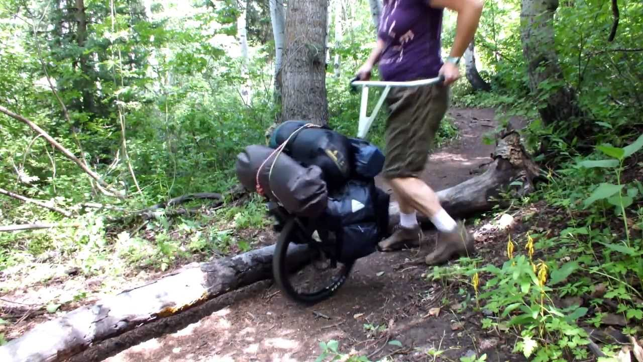 Pack Wheel Hiking Cart Crossing Over A Downed Tree In The