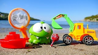 Om Nom & a toy excavator on the beach. Videos for kids.