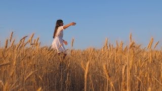 Beautiful Girl in White Dress Dancing in a Field of Ripe Wheat | Stock Footage - Videohive