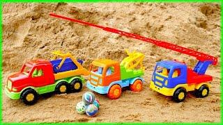 Brincando na areia com caminhões. Os carros juntam as bolas.