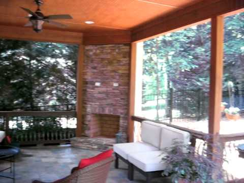 Stone outdoor fireplace integrated in covered raised patio ...