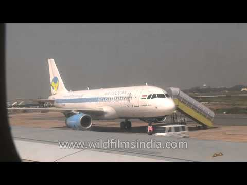 Air Deccan plane being boarded and Jet airways flight to Delhi taxiing at Kolkata Airport