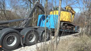 New Holland excavator which had windows shattered gets loaded on a Scania truck April 2015