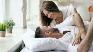 Young beautiful and loving couple wake up at the morning. Attractive woman kiss and hug his husband