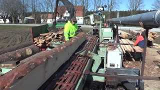 Mobile sawmill on a truck with a blade and movable saw table a man