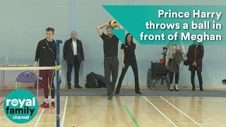 Prince Harry throws a ball in front of Meghan Markle at seated volleyball trials