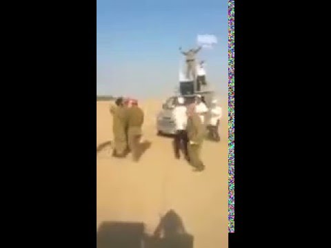Zionist soldiers dance around bombs and celebrate before bombing Gaza.
