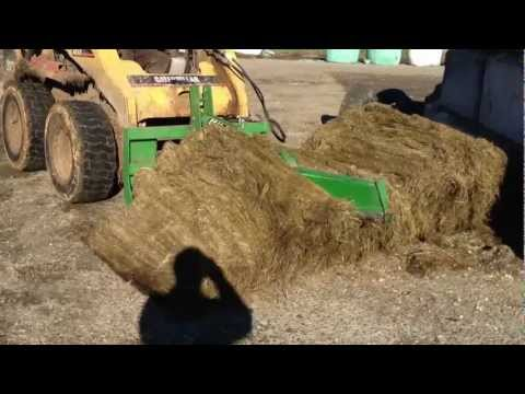 Cutting a round bale in half with Mchale Bale Knive & Caterpillar 262B SkidSteer