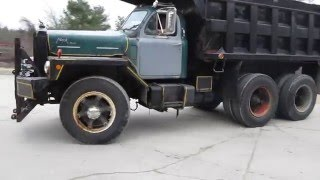 Two Mack dump trucks taking off