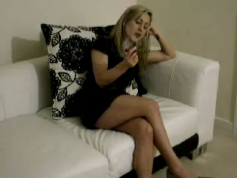 Sexy cigar smoking woman in leather dress