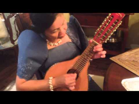 A Filipina Lady Playing A Filipino Musical Instrument In A Traditional Filipina Dress video