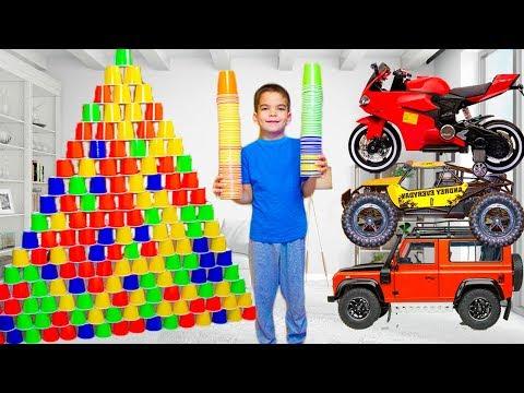 Малыш играет с гигантской пирамидой из стаканчиков катается на машинках и играет с игрушками