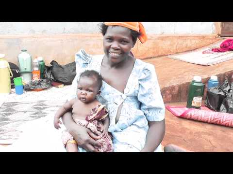 Woman waits for hospital treatment with baby in Jinja, Uganda