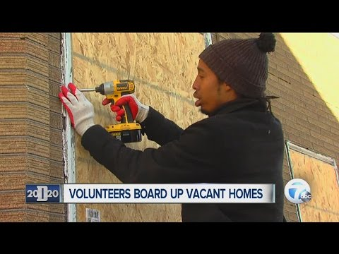 Volunteers board up vacant houses