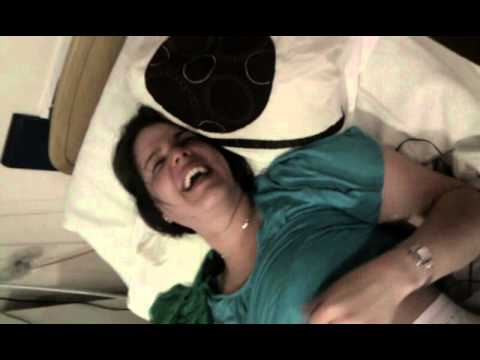 Woman having fun in labor (childbirth). Laughing hysterically on gas and air in labour.