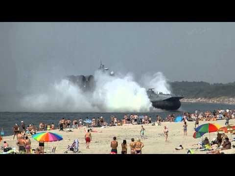 Amphibious landing craft docks at crowded beach in Russia