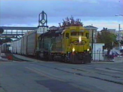 A freight train pulled by Yellowbonnet Santa Fe GP30 #2442 and Burlington Northern green SD40-2 #8003 heads northbound through the street running section in Oakland's Jack London Square. ...