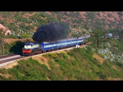A loud and smoky ALCo KJM WDM-2 16669 with Hindupur-Yeshwanthpur passenger chugs into the loop to stop at Makalidurga station. But because of the gradient, h...