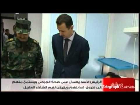 Syrian TV shows President Bashar al-Assad visiting injured troops