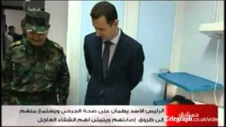 Syrian TV shows President Bashar al-Assad visiting injured troops