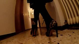 Walking on Casadei open toe leopard pumps with deep black stockings and black skirt